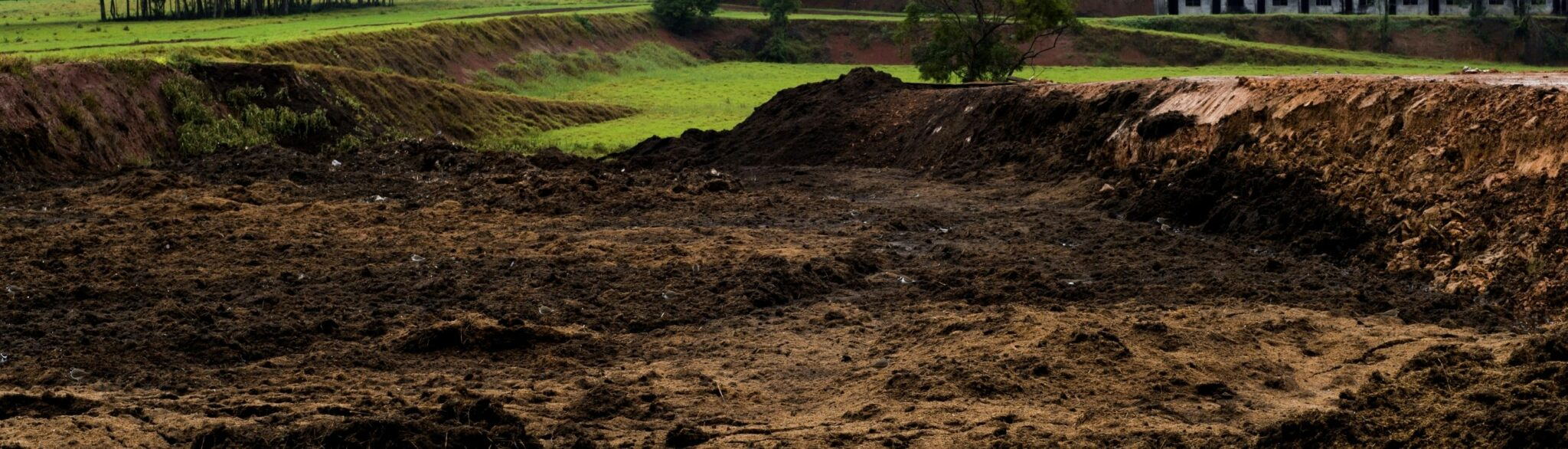 large field with piles of rich loamy soil ready to be added for lawns