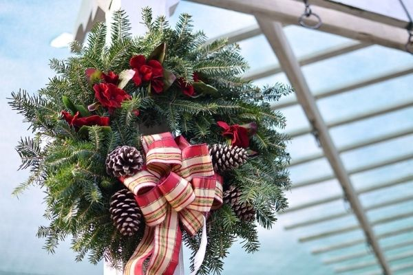 real juniper wreath decorated in red ribbons and pine cones