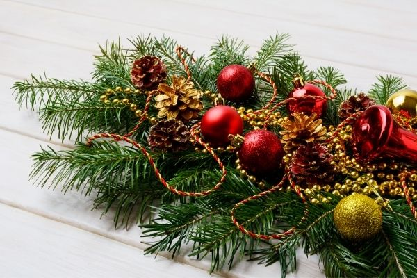 decorated greenery on mantle with red christmas ornaments
